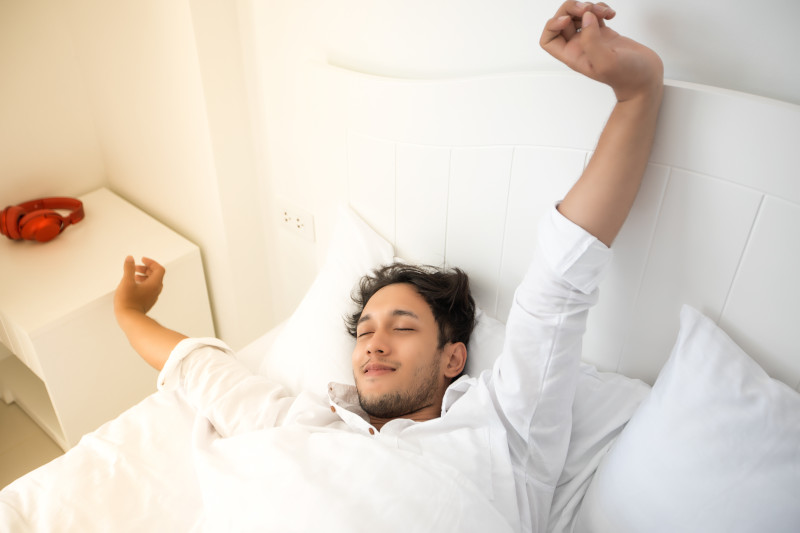 Man stretching while waking up in his bed