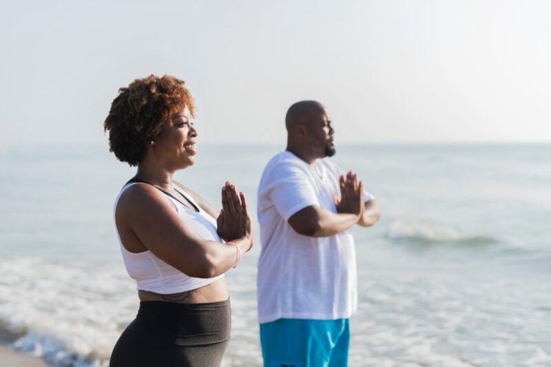 Couple meditating on a beach