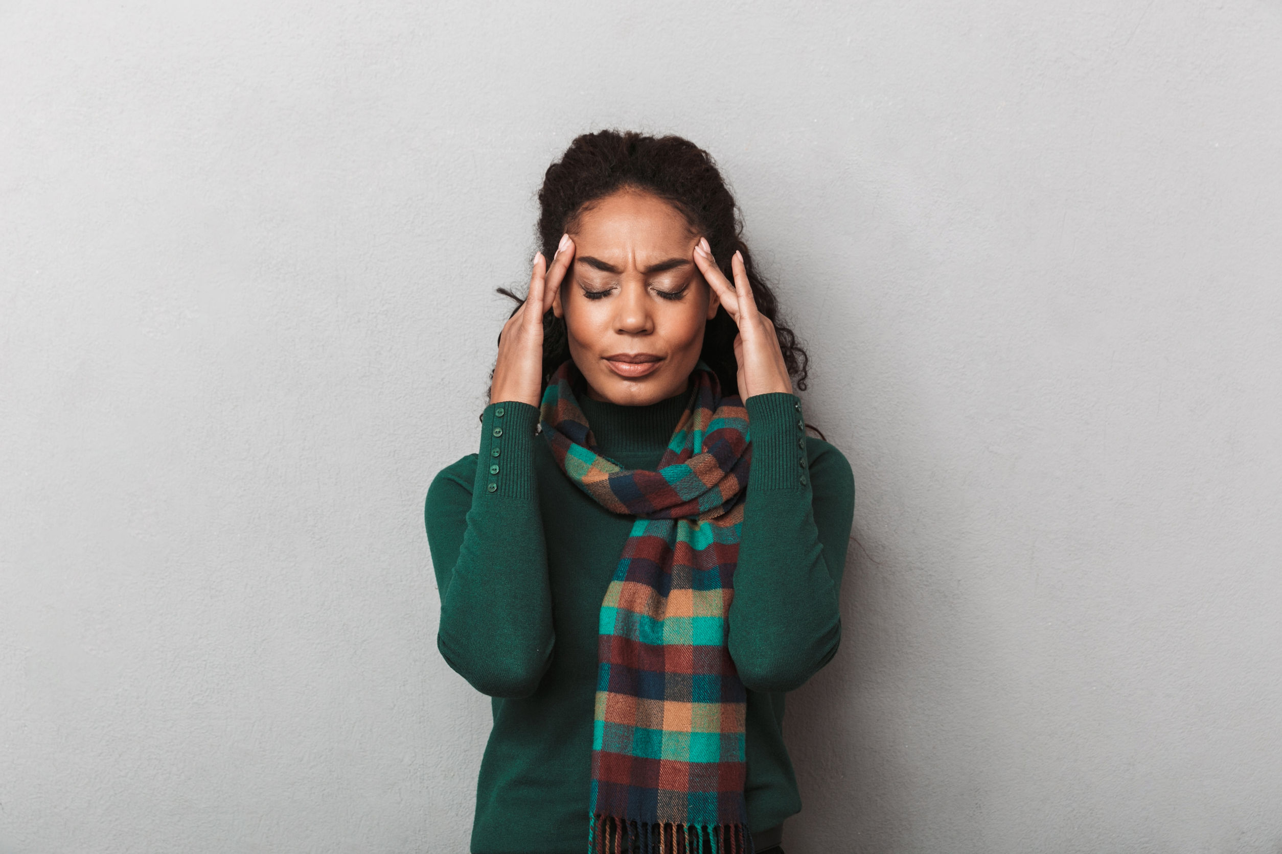 Woman wearing sweater standing over gray wall background, rubbing her temples