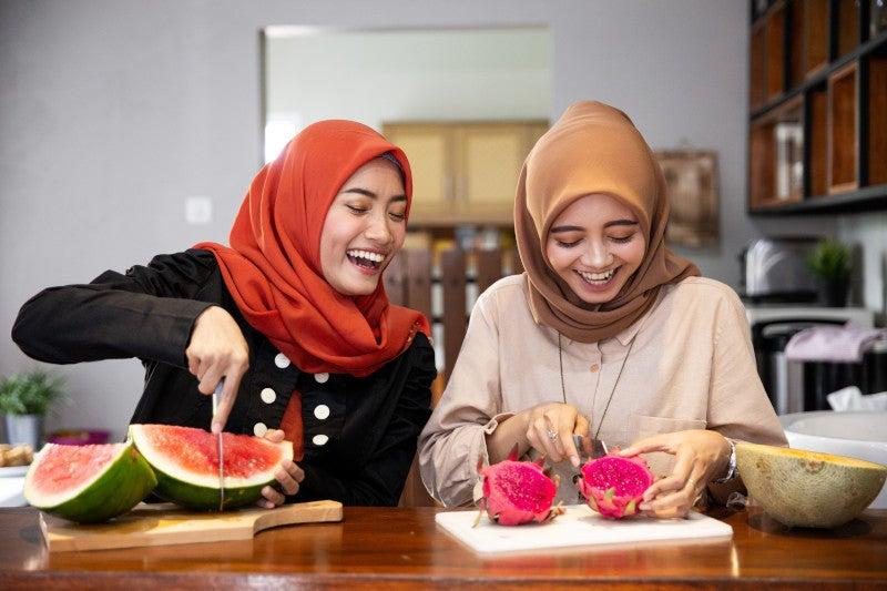 Two women cutting fruit