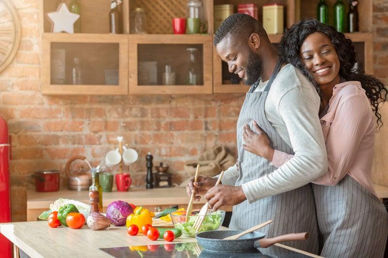 Couple hugging making dinner together