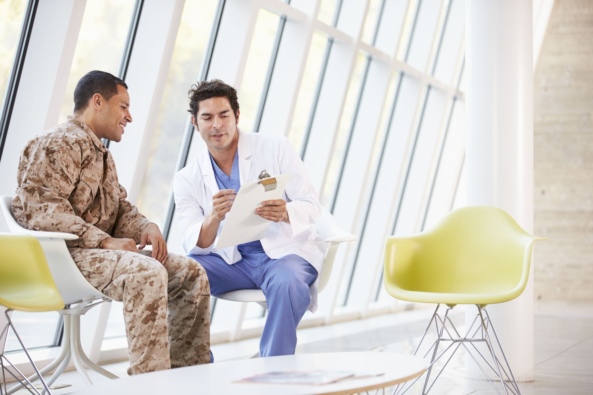 A doctor with a clipboard speaks to a patient wearing fatigues