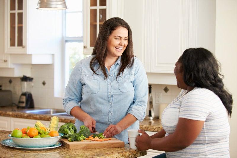 Two Women On Diet Preparing Vegetables in Kitchen