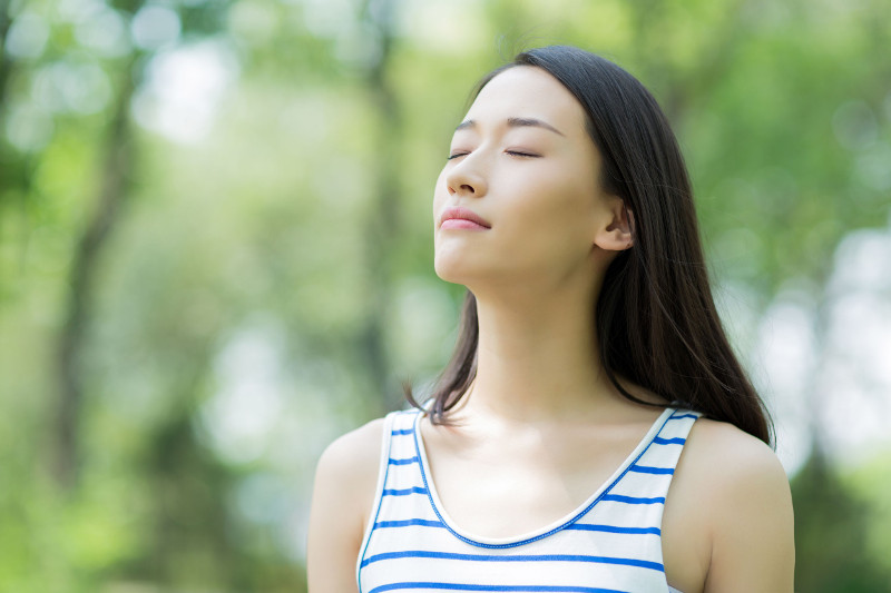 Person peacefully breathing in nature