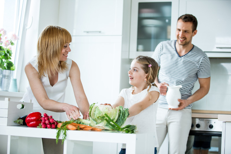 Young family with fresh vegetables in kitchen