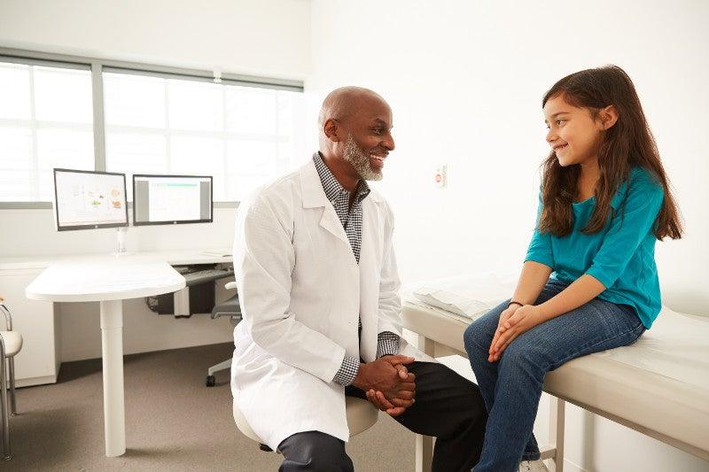 Pediatric Physician in exam room smiling