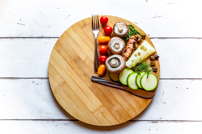 Vegetables on round chopping board shaped like a clock to represent intermittent fasting
